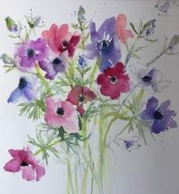 Pink and blue anemones against a white background with sea thistle