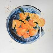 Bright satsumas in a collaged dish.