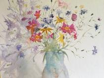 Wild flowers in a mass of colour in a pale blue jug